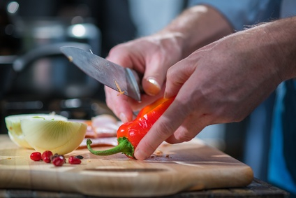 Man cutting red peppers with a knife